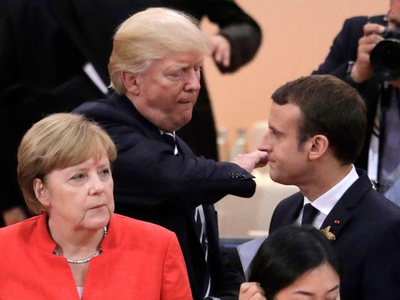 Amor strategic cu năbădăi: Trump și Merkel se ceartă, dar nu divorțează. Macron lăsat cu buzele umflate